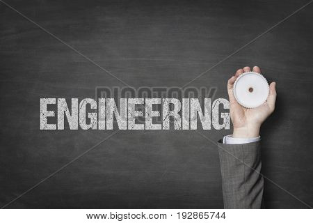 Engineering text with businessman hand holding cogwheel
