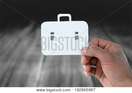 hand holding a schoolbag against wooden table