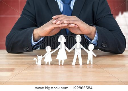 underwriter protecting family in paper with his hands against graphs and numbers