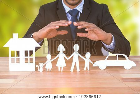 underwriter protecting family in paper with his hands against detail shot of bright green leaves