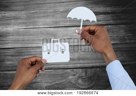 hands holding a schoolbag and an umbrella in paper against close-up of wooden flooring