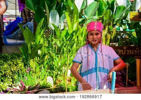 CHIANGMAI THAILAND - JANUARY 24 2015: Hill tribe girl is demonstrating weaving faric in traiditional style in 22nd Traditional Skirt Fabric and The Indigenous Product and Culture Festival in Mae Chaem of Chainagmai Thailand