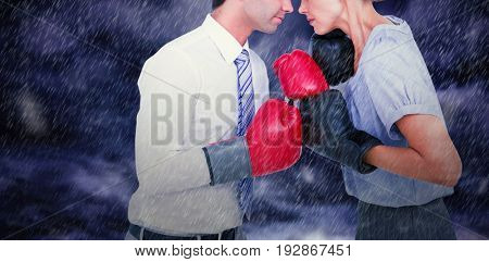 Business people wearing and boxing red gloves against gloomy sky