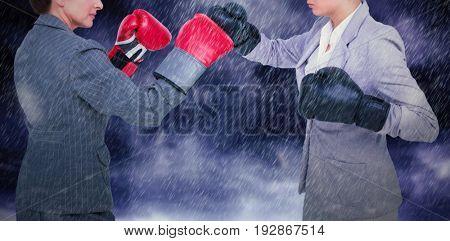 Aggressive businesswomen boxing over white background against gloomy sky