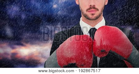 Businessman with boxing gloves against gloomy sky