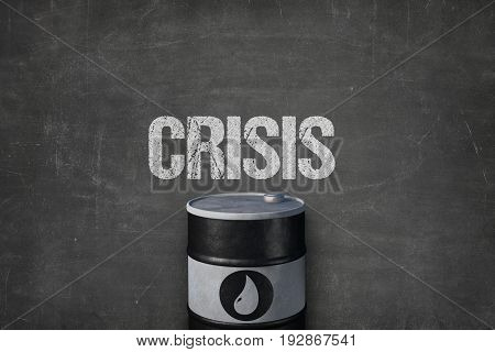 Closeup of metallic oil barrel with symbol under crisis text on blackboard