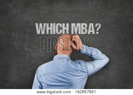 Rear view of confused businessman scratching head under which MBA text on blackboard