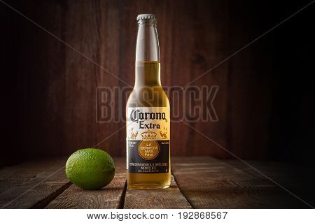 MINSK, BELARUS - APRIL 3, 2017: Editorial photo of bottle of Corona Extra Beer with lime on dark wooden background with copy space. Corona is produced by Grupo Modelo with Anheuser Busch InBev