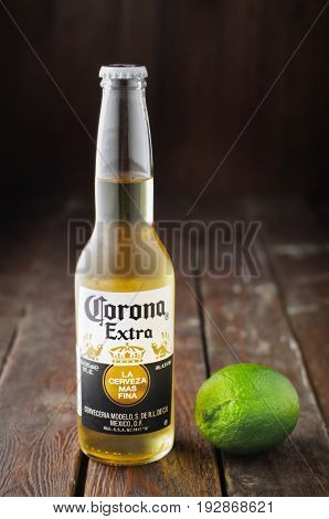 MINSK, BELARUS - APRIL 3, 2017: Editorial photo of bottle of Corona Extra Beer with lime on wooden background. Corona is produced by Grupo Modelo with Anheuser Busch InBev