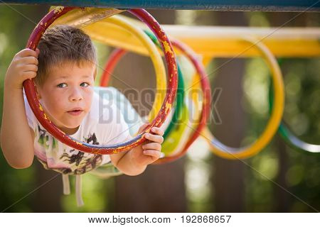 Portrait of cute kid boy lying on the climbing frame. Young boy climbing on playground during summer. Child enjoys climbing through a tunnel in a children's playground outdoors.