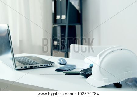 Home Office Of An Architect With White Helmet, Laptop Pc And Drawing Accessories