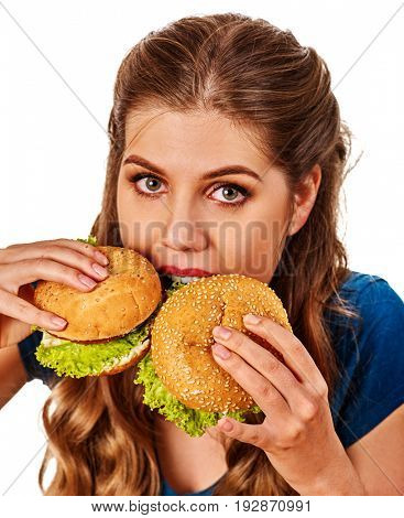Woman eating hamburgers. Portrait of student consume fast food on table. Girl trying to eat junk against diets. One burger is more delicious than other.