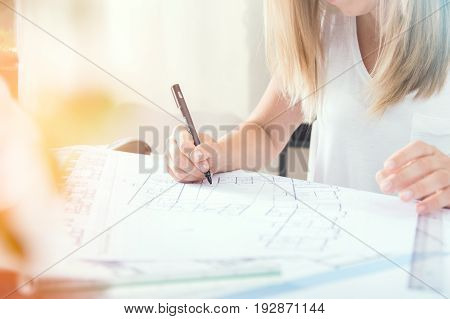 Young blonde architect is making professional architectural plan