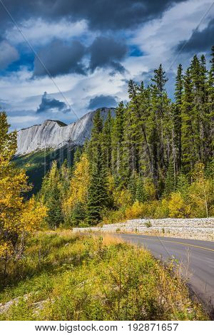 Cloudy autumn day in the Canadian Rockies. The asphalt road runs between mountain peaks