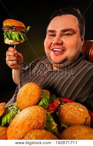 Fat man eating fast food hamberger. Breakfast on fork for overweight person. Junk meal leads to obesity. Person regularly overeats concept on black background. Foods high in fat concept.