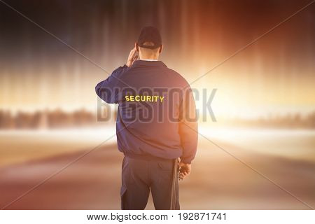 Rear view of security officer listening to earpiece against city on the horizon