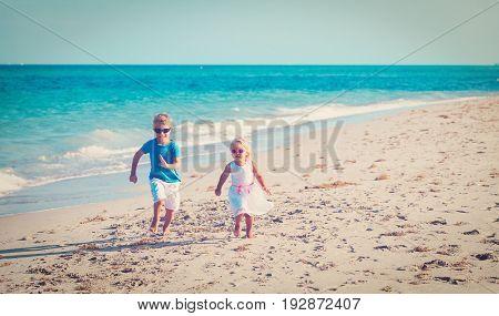 little boy and girl running on tropical beach