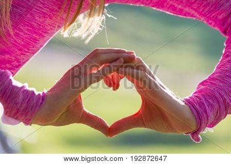 Hand on heart on green summer background
