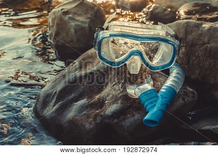Mask For Diving And Snorkel Tube Lie on The Stones On The Sandy Closeup. Tourism Travel Freediving Concept