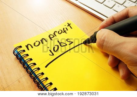 Man is writing non profit jobs in a note.
