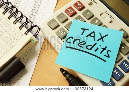 Memo stick with words tax credits. Business concept.