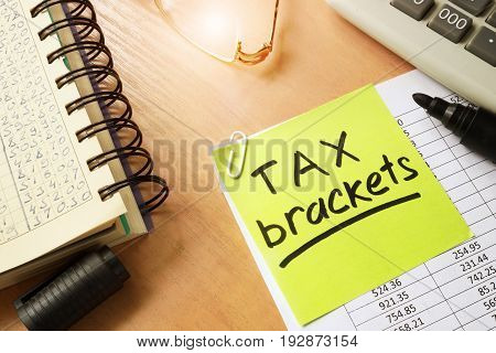 Memo stick with words tax brackets. Business concept.