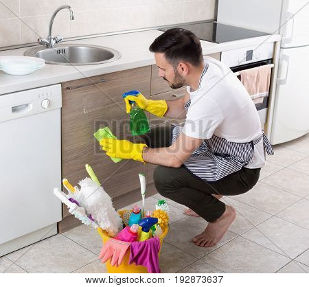 Man Wiping Kitchen Cabinets