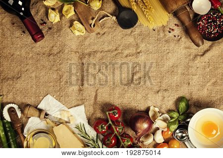 Italian food background with vine tomatoes, basil, spaghetti, spinach, onion, parmesan, olive oil, garlic, peppercorns, rosemary and eggs. Burlap background