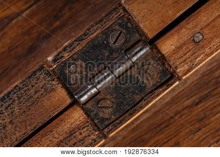 Door Hinges Against A Wooden Background. Rusty Iron Details On A Dark Wooden Background.