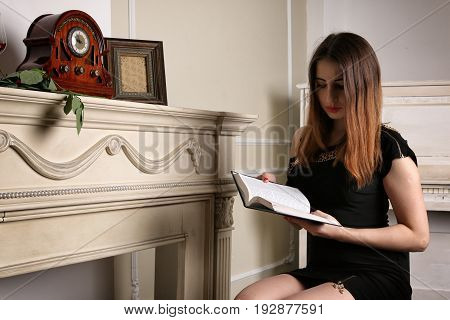 Young woman in black dress reading book near to fireplace. Studio lighting