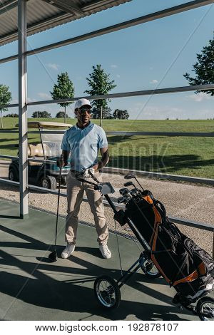 Stylish Golf Player With Golf Club In Hand Standing Near Golf Bag