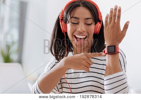 Smart watch. Happy joyful young woman smiling and looking at you while pointing at her smart watch