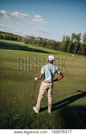 Back View Of Golfer Holding Club And Looking Away At Green Lawn