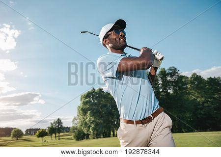Smiling African American Man In Cap And Sunglasses Playing Golf