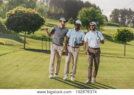 Confident Smiling Men In Caps And Sunglasses Holding Golf Clubs And Walking On Lawn
