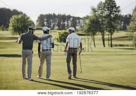 Back View Of Multiethnic Golf Players Hugging And Walking On Golf Course