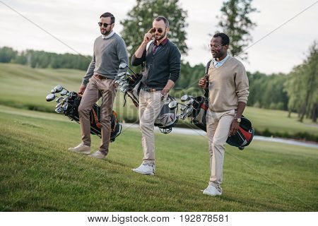 Stylish Multiethnic Friends Holding Bags With Golf Clubs And Walking On Golf Course