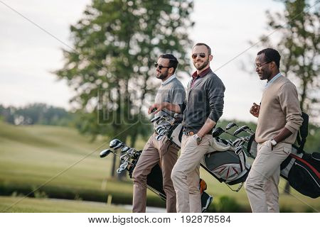 Stylish Multiethnic Men Holding Bags With Golf Clubs And Walking On Golf Course