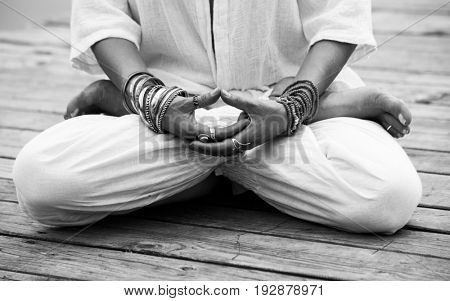 woman hand in yoga symbolic gesture mudra wearing lot of bracelets and rings outdoor on wooden pontoone closeup