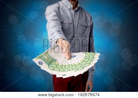 Young businessman holding large amount of bills with shiny blue background