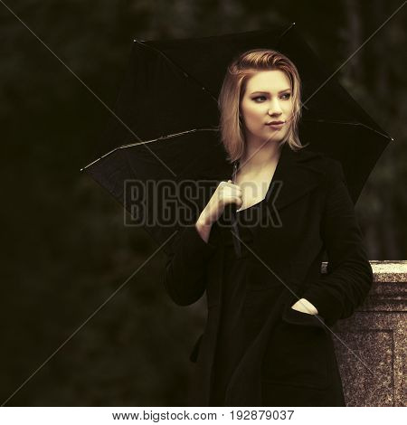 Sad young fashion woman with umbrella in the rain. Stylish female model in black coat outdoor