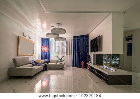 Room in a modern style with white walls and light tiled floor. There is a burning fireplace on the tabletop with decorations, TV, shelves, red vase, glass chair, sofas, luminous fancy red lamp.