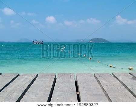 Seaside boardwalk with emerald sea and boat
