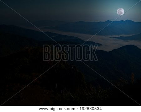 Mountain and mist with full moon at midnight.