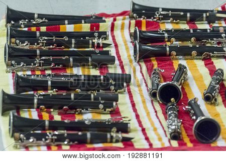several clarinets resting on a beach towel at rehearsal