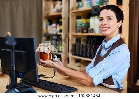 Middle-aged shop assistant looking at camera with charming smile while scanning barcode of jar with peach jam