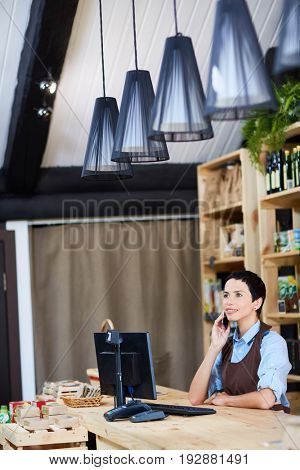 Cheerful middle-aged shop owner talking to her friend on smartphone while having short break in small store with organic products, waist-up portrait