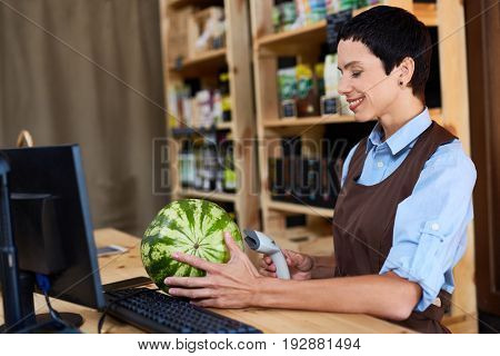 Profile view of beautiful middle-aged cashier scanning barcode of watermelon in small store with organic food, waist-up portrait