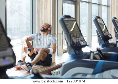 Portrait of modern trendy  sportsman sitting  in sunlight by window listening to music in big headphones with eyes closed, resting after gym workout behind row of treadmills