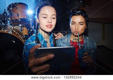 Portrait of two trendy teenage girls taking selfie in club, posing seductively